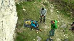 4K Rock climbing group checking equipment & preparing for a climb Stock Footage