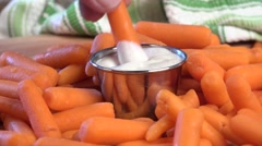 Dipping carrots in salad dressing Stock Footage