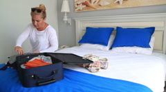 Woman in hotel room packing suitcase 4 - stock footage