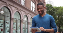 Young African American black man in city using tablet pc computer - stock footage