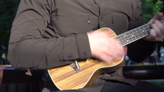 Musician Playing in the Park on a Small Guitar Stock Footage