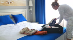Woman in hotel room packing suitcase Arkistovideo