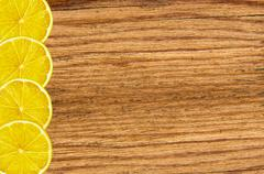 Yellow juicy lemon slice on wood texture close-up background Stock Photos