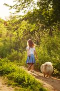 Little girl walking with a dog Stock Photos