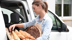 Cheerful baker delivering bread to client - stock footage