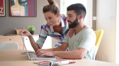 Couple at home looking at decoration website on laptop - stock footage