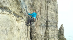 4K Young woman climbing vertical rock face trying to find a strong grip - stock footage