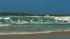 Tracking shot of surf ski competitors leaving the beach in a race Stock Footage