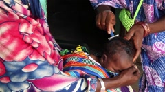 Africa native village shaving head of baby to prepare for baptism Stock Footage