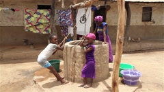 Africa native village woman and children in well Stock Footage