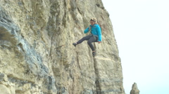 4K Female climber descends rocky cliff to join other climbers on the ground Stock Footage