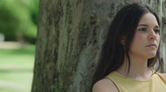 Young woman thinking upset in the park. Close up. Dolly shot Stock Footage