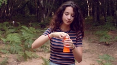 Slow motion shot of girl having fun with soap bubbles in the forest Stock Footage