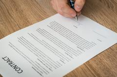 Businessman signing a contract to conclude a deal - business concept Stock Photos