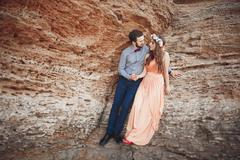 Romantic loving couple walking on the beach with rocks and stones Stock Photos