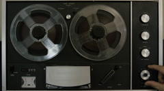 A caucasian hand starts a vintage Reel-to-reel tape. It plays for 30 seconds. Stock Footage