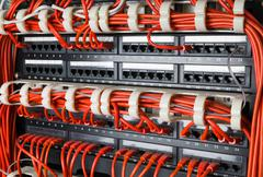 Rows of network cables connected to router and switch hub - stock photo