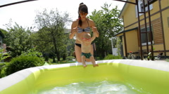 Mom With a Child Splashing in the Pool - stock footage