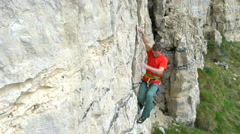 4K Young man climbing vertical rock face trying to find a strong grip Stock Footage