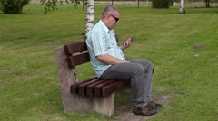 Stressful man with tablet PC in the park on bench Stock Footage