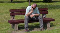 Stressful man with tooth pain in the park on bench Stock Footage