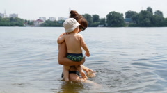Mom With a Child on the Riverbank - stock footage