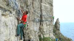4K 2 people climbing natural vertical rock face - England, UK. - stock footage