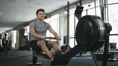 Man doing exercise on fitness machine in gym Stock Footage