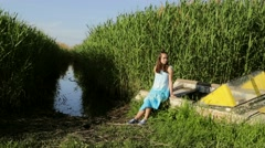Young teenage girl sitting on old boat near lake rural green reeds background Stock Footage