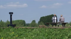 Two men sit on a bench in river landscape - wide shot Stock Footage