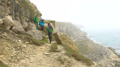 4K Active friends with climbing equipment standing on cliff & looking out to sea - stock footage