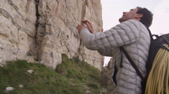 4K Rock climbers standing at base of cliff & planning their climb Stock Footage