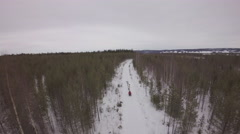 Aerial view of sled dogs running through a trail in winter forest - Sweden Stock Footage