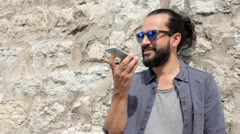 Smiling man with smartphone calling on city street. Stock Footage