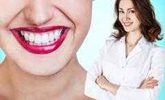 picture of attractive female dentist with tools - stock photo