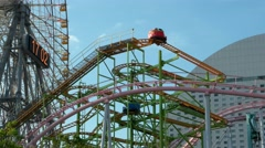 Yokohama - Amusement park attractions with ferris wheel at Yokohama Cosmoworld. - stock footage