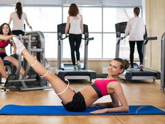 Young woman doing exercise on press - stock photo