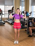 Woman doing exercise with dumbbell in the gym - stock photo