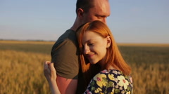 A couple hug, kiss and then walk in a wide open golden field at sunset Stock Footage