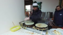 Сelebration of Maslenica carnival in Moscow, Russia. Man cooking pancakes Stock Footage