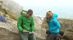 4K Active couple with climbing equipment standing on cliff looking at guide book Stock Footage