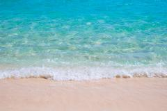 Sand beach and blue sea wave Stock Photos