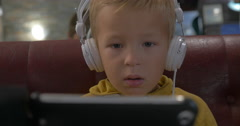 Kid in headphones watching cartoon on smart phone Stock Footage