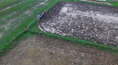 Aerial top view of a farmer and its rototiller in muddy field Stock Footage
