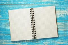 checked notebook on wood - stock photo