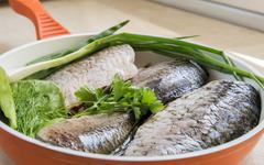 Fish and components for her preparation in a large skillet. Stock Photos