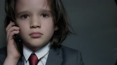 4k shoot of a cute child posing as a business man in studio with a phone Stock Footage