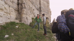 4K Group of rock climbers standing at base of cliff & planning their climb Stock Footage