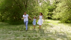 Happy family running in a beautiful park while holding hands with eachother Stock Footage