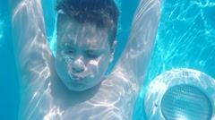 Teen Boy Dives in Blue Pool With Closed Eyes and Make Some Bubbles . Slow Stock Footage